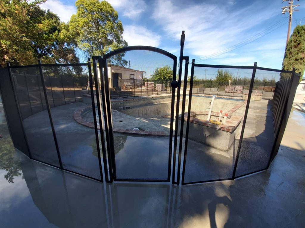 mesh pool fence with self-closing gate installed in Courtland, CA
